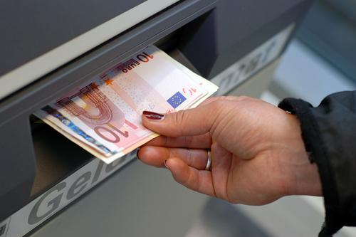 A woman receives european money at an atm in germany.