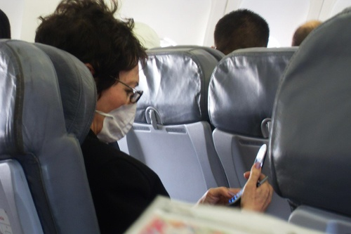 A woman guards herself from germs on a commercial flight.