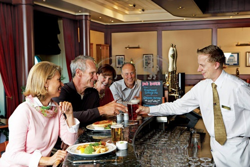 Model passengers down a pint with lunch at Queen Mary 2's Golden Lion Pub. Photo: Courtesy of Cunard Line