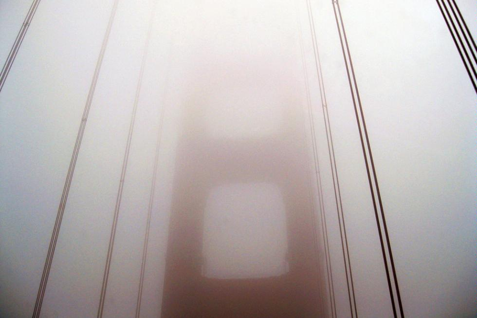 The Golden Gate Bridge being obscured by the fog in San Francisco, California.