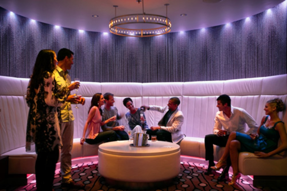 Group of friends having drinks at Quasar nightclub onboard Celebrity Solstice.
